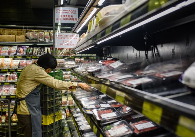 This file photo taken on March 21, 2017 shows a member of staff clearing packs of imported meat from Brazil off the shelves of a supermarket in Hong Kong