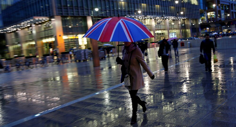 Workers walk in the rain at the Canary Wharf business district in London, Britain November 11, 2013.