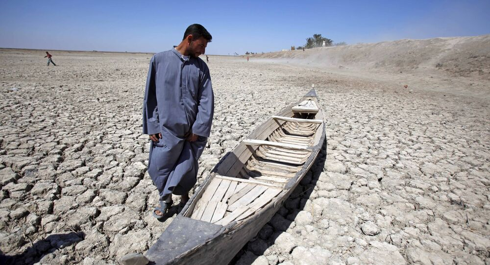 In this photo taken Friday, March 27, 2009, Akeed Abdullah stands next to his boat in a dried marsh in Hor al-Hammar in southern Iraq