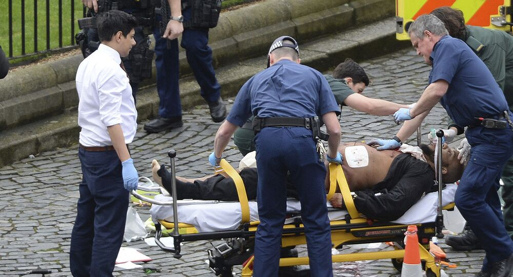 FILE- In this March 22, 2017 file photo, the attacker Khalid Masood is treated by emergency services outside the Houses of Parliament London. British Police named on Thursday March 23, 2017, Khalid Masood as The Houses of Parliament attacker