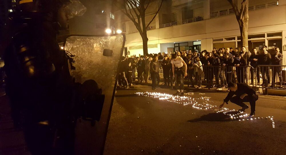Youths use candles to write the word Violence in the road in front of a line of riot police outside the commisariat of the 19th Arrondissement (District) of Paris late on March 27, 2017, during clashes in the wake of the death of a Chinese national during a police intervention.