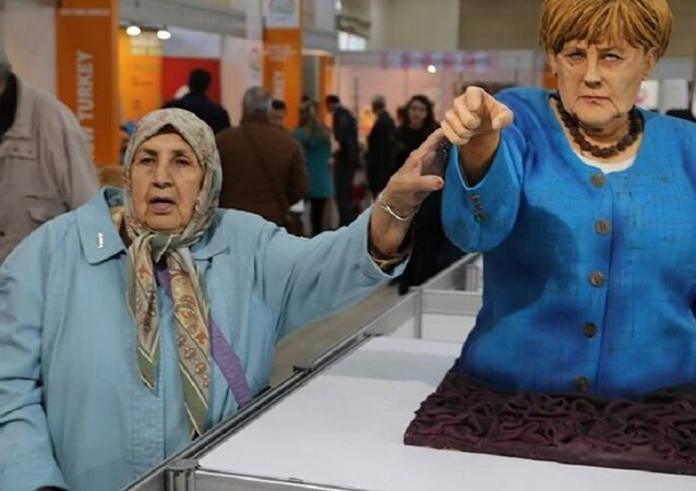 A visitor takes a picture next to the cake bust of German Chancellor Angela Merkel by Turkish confectioner Tuba Geçkil at the Festival of Chocolates, Sweets and Cakes in Istanbul.