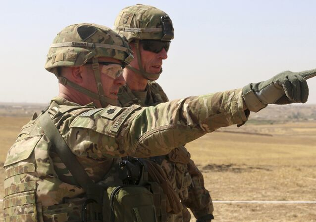 This Oct. 10, 2016 photo released by the U.S. Army shows U.S. Army Lt. Col. Ed Matthaidess, commander, left, Task Force Falcon, outlining areas of an Iraqi security forces tactical assembly area to U.S. Army Maj.
