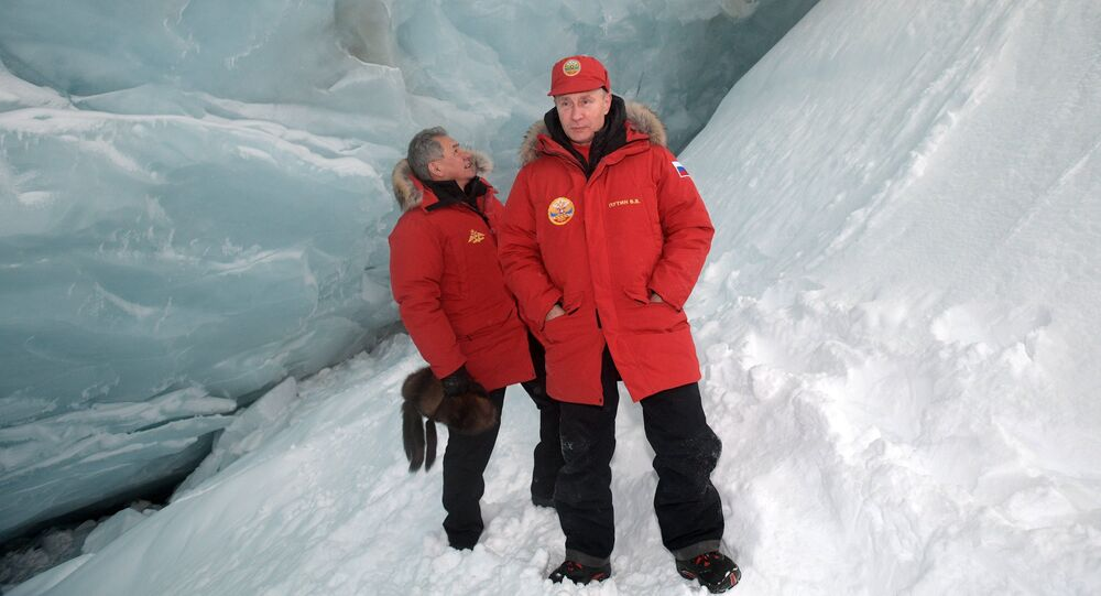 Russian President Vladimir Putin, foreground, and Defense Minister Sergei Shoigu, inspect a cavity in a glacier on the Arctic Franz Josef Land archipelago in Arctic Russia