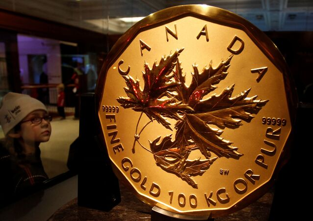 A visitor to the Royal Canadian Mint looks at a 100 kg solid gold coin during the Vancouver 2010 Winter Olympics