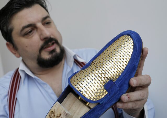 Antonio Vietri, artisan and founder of A&V Fashion, shows a man shoe as part of his collection Gold on March 16, 2017 in his workshop in Turin. Antonio Vietri made a crazy bet: selling 24-carat gold plaited shoes targeting customers of the Gulf countries.
