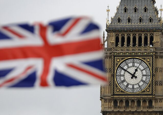 British Union flag waves in front of the Elizabeth Tower at Houses of Parliament containing the bell know as Big Ben in central London