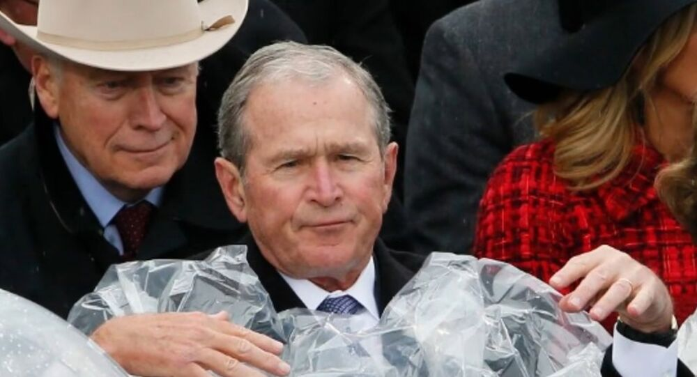 George W. Bush struggles to put on a poncho during Donald Trump's inauguration.