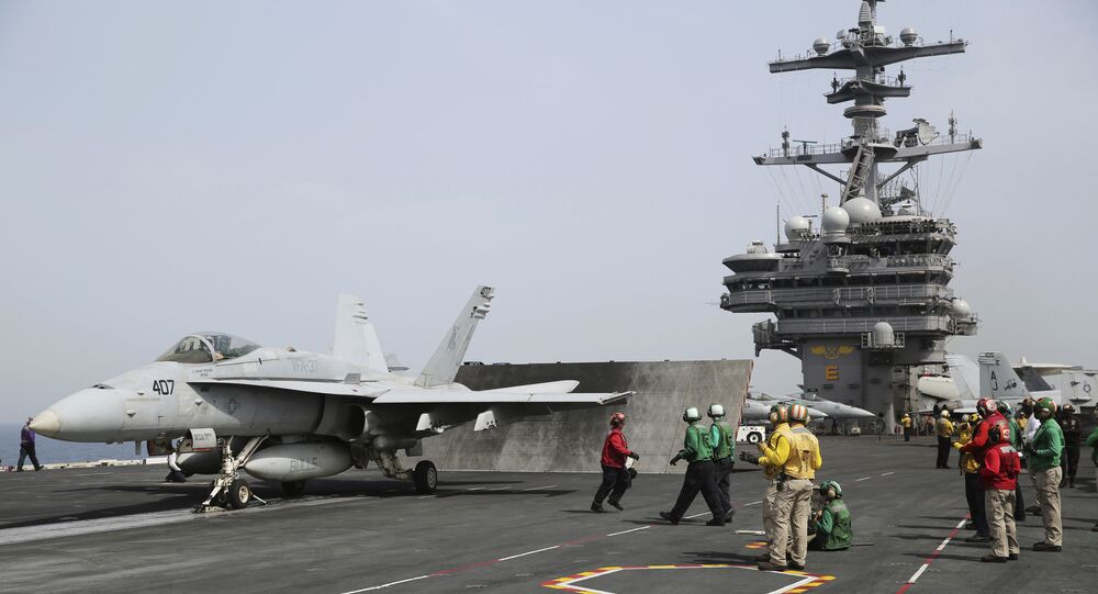 In this Wednesday, March 22, 2017 photograph, sailors prepare to launch an F-18 off of the USS George H.W. Bush as it travels through the Persian Gulf.