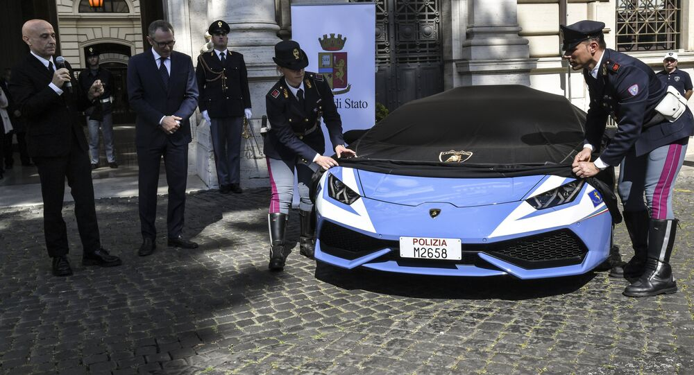 Italy's Interior Minister Marco Minniti (L) unveils the new police's car Lamborghini Huracan next to Stefano Domenicali, Chief Executive Officer of Automobil Lamborghini, during a press conference at the Interior Ministry Viminale in Rome, on March 30, 2017.
