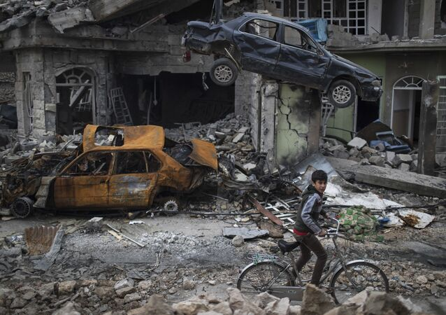 A boy rides his bike past destroyed cars and houses in a neighborhood recently liberated by Iraqi security forces, on the western side of Mosul, Iraq, Sunday, March 19, 2017