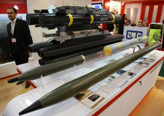 An exhibitor staff stands beside missiles and rockets manufactured by Roketsan in Turkey at the 12th Defence Services Asia Exhibition and Conference in Kuala Lumpur, Malaysia, Monday, April 19, 2010