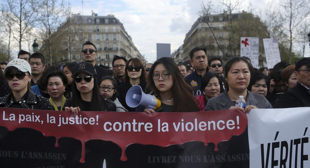 People from the Chinese community holds a banner reading  For peace and justice, against violence as they protest over the fatal shooting of Shaoyo Liu in his apartment, in Paris, Sunday, April 2, 2017.