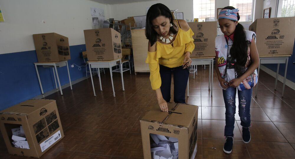 A woman deposits her ballot during the presidential runoff election Quito, Ecuador, Sunday, April 2, 2017