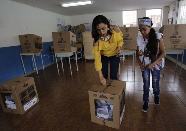 A woman deposits her ballot during the presidential runoff election Quito, Ecuador, Sunday, April 2, 2017