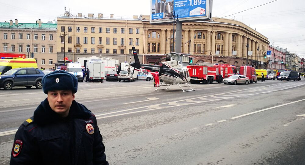 Emergency vehicles and a helicopter are seen at the entrance to Technological Institute metro station in Saint Petersburg on April 3, 2017