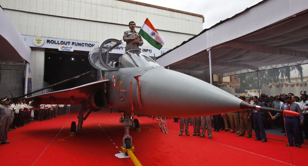 A Hindustan Aeronautics Limited engineer hurls the Indian flag as he stands in the cockpit of India's first indigenous naval Light Combat Aircraft LCA (Navy) NP1 during its roll out ceremony in Bangalore, India, Tuesday, July 6, 2010