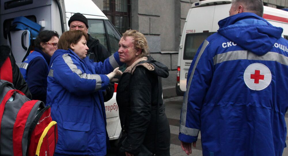 Medics help an injured woman outside Technological Institute metro station in Saint Petersburg on April 3, 2017