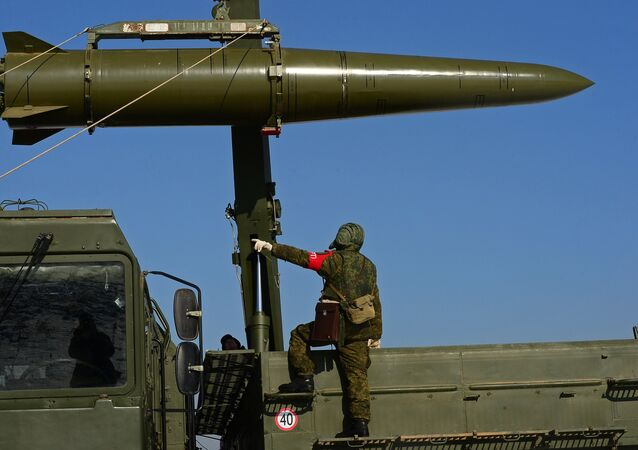 A Russian soldier watches a transporter-loader place an Iskander-M shorter-range missile onto a self-propelled launcher during an exercise involving missile and artillery units of the Eastern Military District's Fifth Russian Army in the Primorye Territory