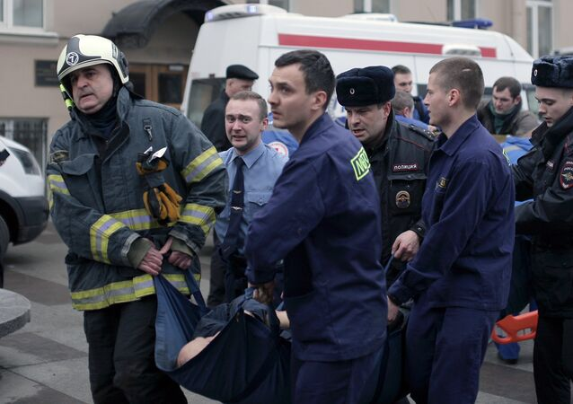 Police and emergency services personnel carry an injured person on a stretcher outside Technological Institute metro station in Saint Petersburg on April 3, 2017