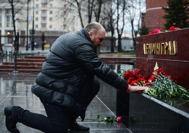 Мужчина возлагает цветы к тумбе города Ленинград на Аллее Городов-героев в Москве в память о погибших в результате взрыва в метрополитене Санкт-Петербурга
