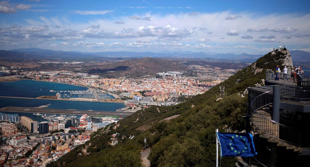 A general view shows the Spanish city of La Linea de la Concepcion (rear) and the tarmac of the Gibraltar International Airport (bottom L) while tourists stand on the top of the Rock (R) next to the European Union flag, in the British overseas territory of Gibraltar, September 14, 2016