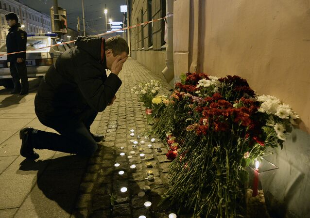 A man reacts as he places flowers in memory of victims of the blast in the Saint Petersburg metro outside Technological Institute station on April 3, 2017