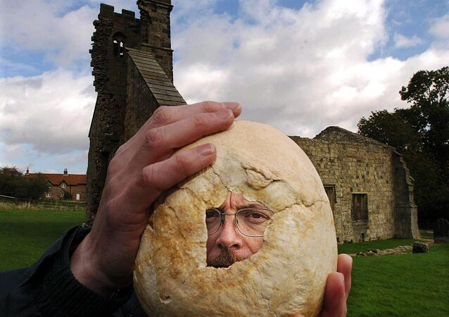 Simon Mays, the Skeletal Biologist at English Heritage's Centre for Archaeology, examines the hole in the skull, Tuesday Oct. 5, 2004, discovered at Wharram Percy, a deserted medieval village near Leeds, England