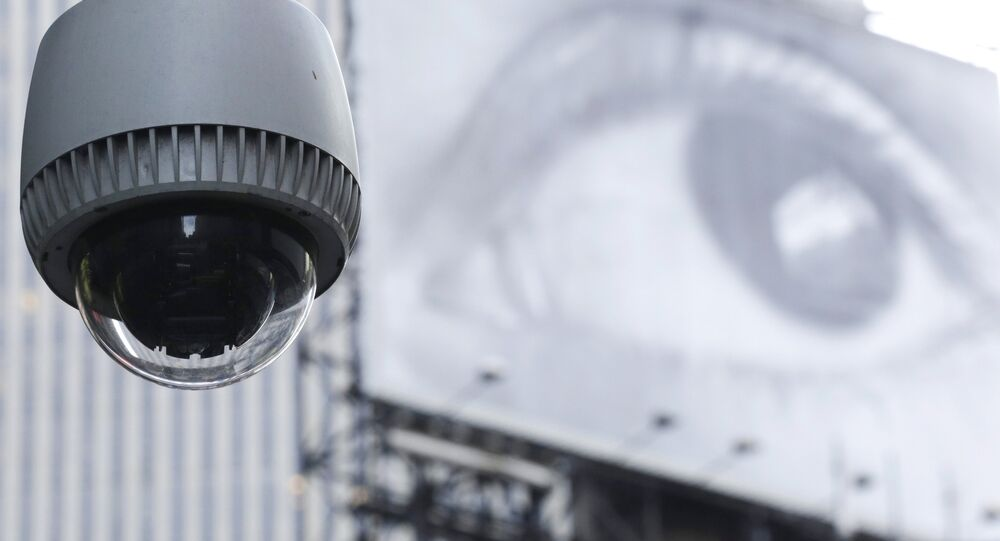 A security camera is mounted on the side of a building overlooking an intersection in midtown Manhattan