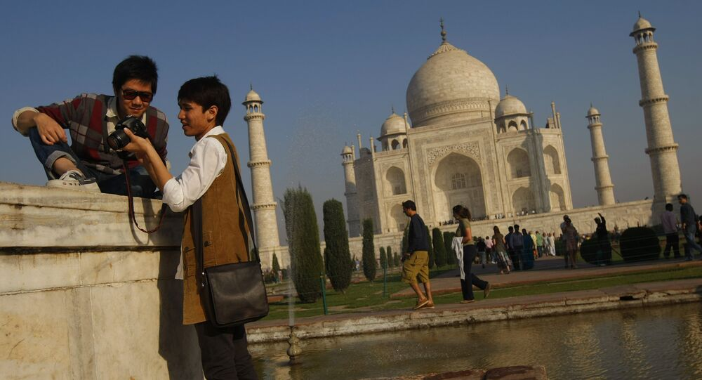 Tourists look at their camera after taking a picture near the UNESCO World Heritage site Taj Mahal in Agra.
