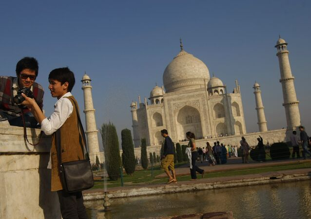 Tourists look at their camera after taking a picture near the UNESCO World Heritage site Taj Mahal in Agra