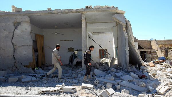 Civil defense members inspect the damage at a site hit by airstrikes on Tuesday, in the town of Khan Sheikhoun in rebel-held Idlib, Syria April 5, 2017 - Sputnik International