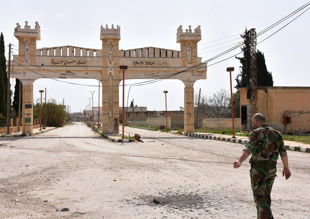 A member of the Syrian government forces walks in Deir Hafer on the eastern outskirts of Aleppo on March 30, 2017, after they took control of the town from Daesh terrorists