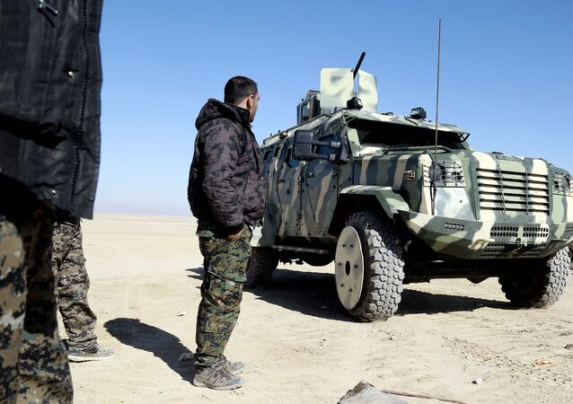 A fighter from the Syrian Democratic Forces, inspects a military vehicle supplied by the US-led coalition, as they gather near a village north-east of Raqa