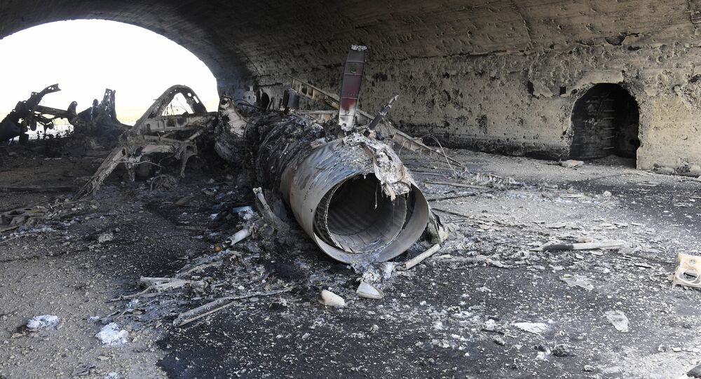 The body of a plane burned as a result of the US missile strike on an air base in Syria