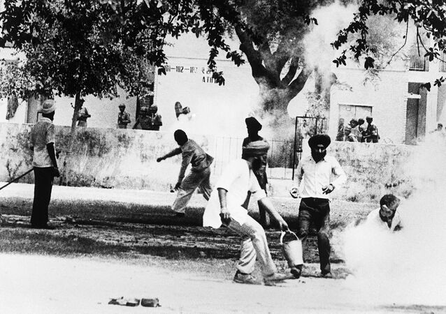 Sikhs militant throw a tear gas canister back at indian police after it was fired to breakup violence around the Gurdwara Bangla Sahib, also known as Golden Temple, for the second day on June 07, 1984, as the news of death of the Sikh leader Jarnail Singh Bhindranwale in Amritsar, Punjab.