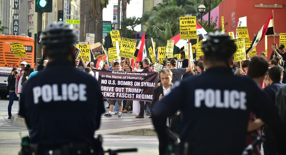 Police watch as demonstrators protest US air strikes against Syria