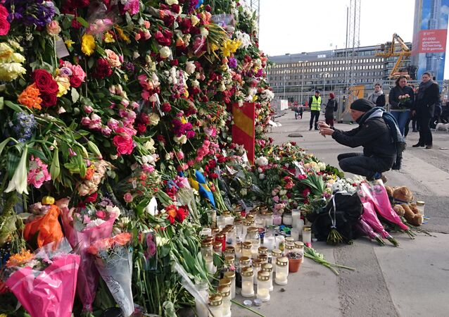 A man takes a picture of flowers on the fence by Ahlens department store following Friday's attack in central Stockholm, Sweden, April 9, 2017