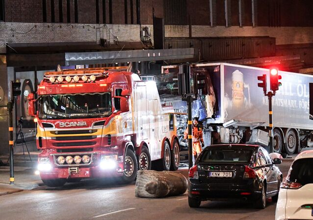 Tow trucks pull away the beer truck that crashed into the department store Ahlens after plowing down the Drottninggatan Street in central Stockholm, Sweden, April 8, 2017