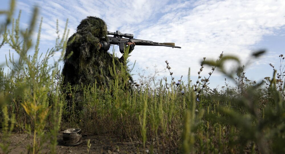 A Ukrainian sniper holds on the position of Ukrainian forces on frontline in the Lugansk region on August 27, 2015