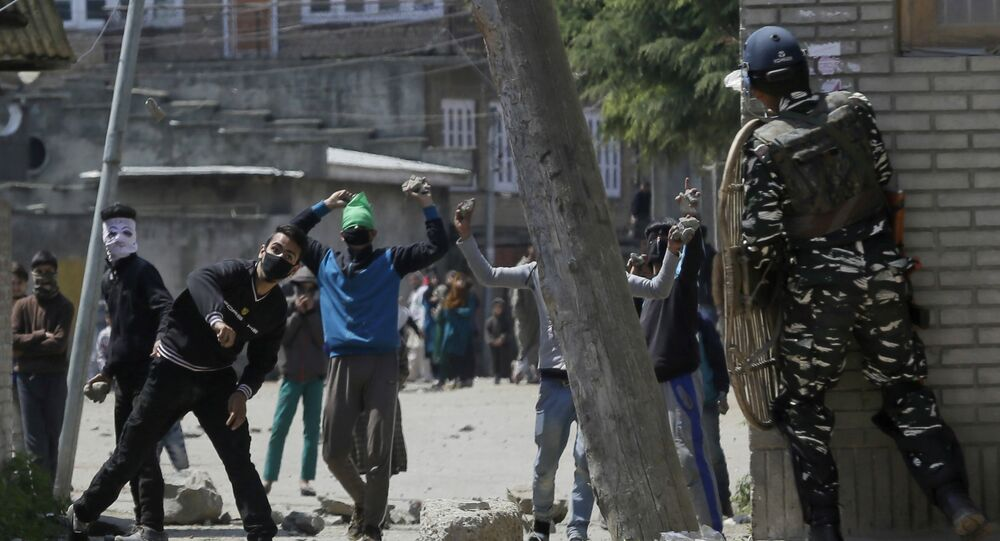 Kashmiri protesters throw stones on Indian security men outside a poling station during a by-election to an Indian Parliament seat in Srinagar, Indian controlled Kashmir, Sunday, April. 9, 2017