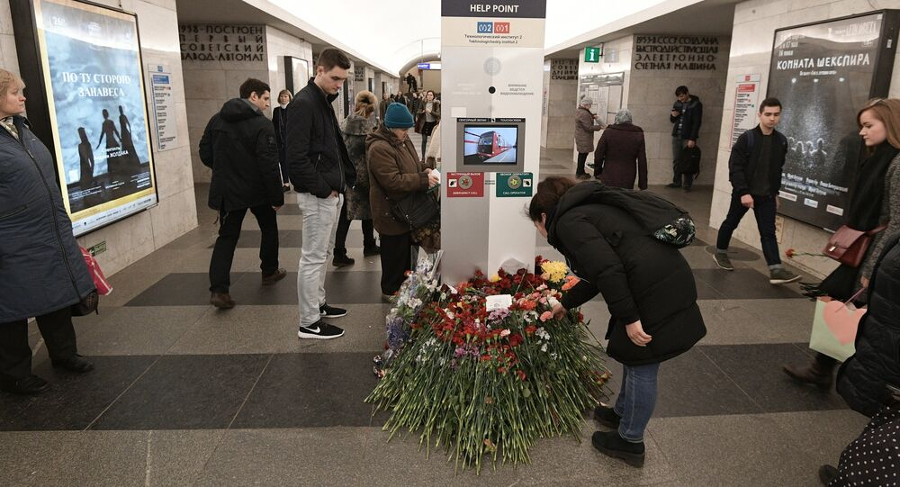 People lay flowers at the Tekhnologichesky Institut metro station in memory of the St. Petersburg Metro explosion victims