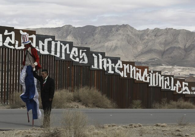 Protestors dressed as a diabolical Uncle Sam, on stilts, and Mexico's President Enrique Pena Nieto hold hands as they walk along the border fence in Ciudad Juarez, Mexico Sunday, Feb. 26, 2017.