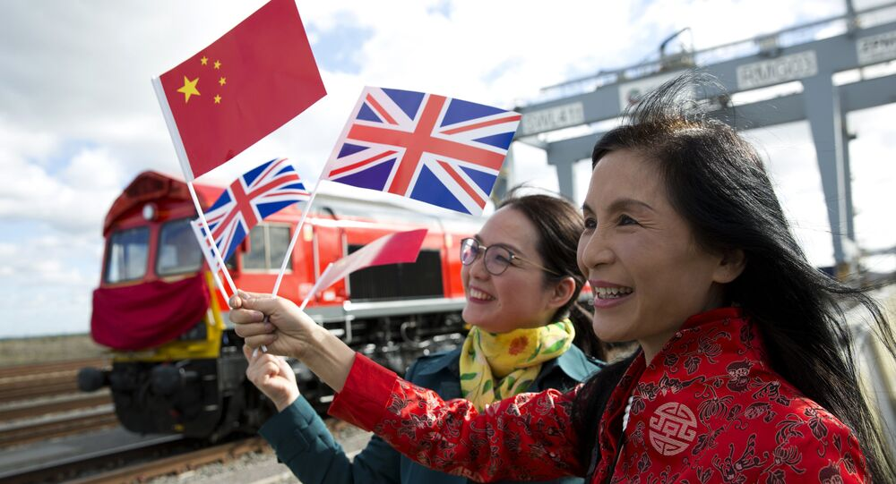 People wave a Chinese and a Union flags as they pose for photographs during a photcall to witness the departure of a freight train transporting containers laden with goods from the UK, from DP World London Gateway's rail freight depot in Corringham, east of London, on April 10, 2017, enroute to Yiwu in the eastern Chinese province of Zhejiang.