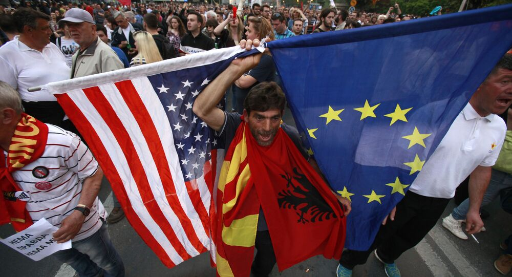 A protestor holds the flags of the United States, Macedonia, Albania and the European Union while attending a march through downtown Skopje, Macedonia, Monday, April 18, 2016