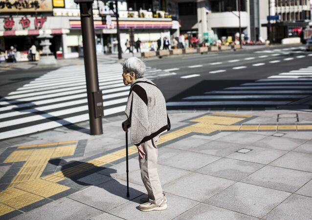 A Japanese elderly woman waits for the traffic light to cross the street in Nagano, northwest of the capital Tokyo on November 7, 2016