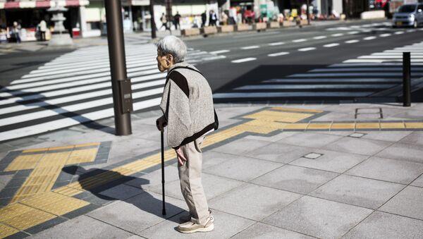 A Japanese elderly woman waits for the traffic light to cross the street in Nagano, northwest of the capital Tokyo on November 7, 2016 - Sputnik International