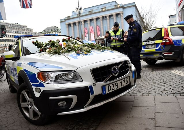 Flowers lay on a police car at Hotorget square near the crime scene in central Stockholm on April 8, 2017, the day after a hijacked beer truck plowed into pedestrians on Drottninggatan and crashed into Ahlens department store, killing four people, injuring 15 others