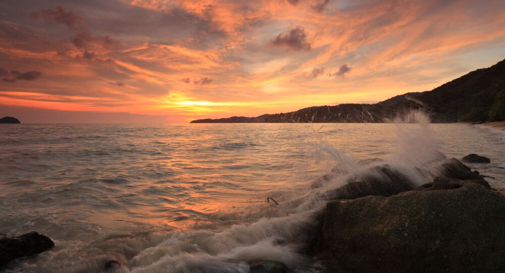 Image of of crashing waves over the sunset in the Indian Ocean beach near Malaysia