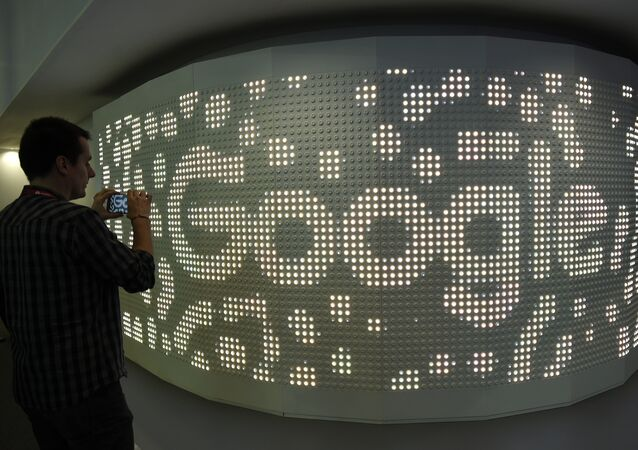 A visitor takes a picture with his mobile phone at the stand of Google on the second day of the Mobile World Congress on February 28, 2017 in Barcelona